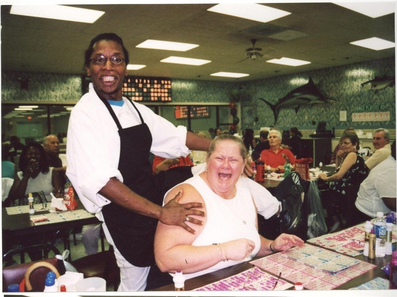 A man standing over an excited women playing bingo