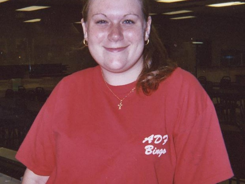 A woman in a red shirt smiling