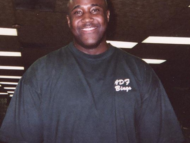 A man in a black shirt smiles at the camera