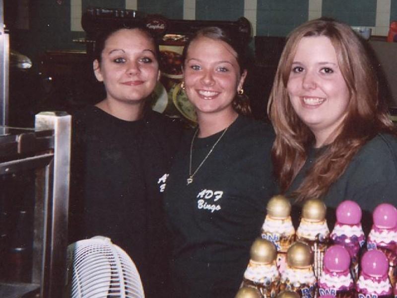three women in matching shirts smile