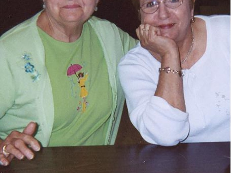 two ladies smile and lean on a table