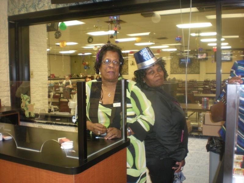 women pose behind counter