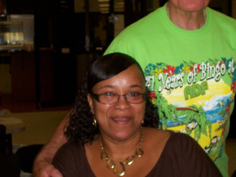 woman in green shirt with arm around sitting woman