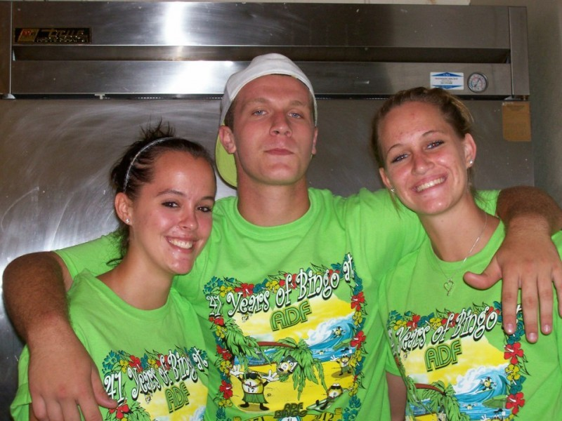 man with arms around two women all in green shirts