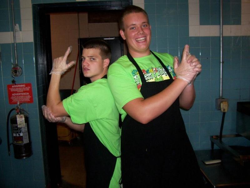 two young guys do finger gun pose in green shirts