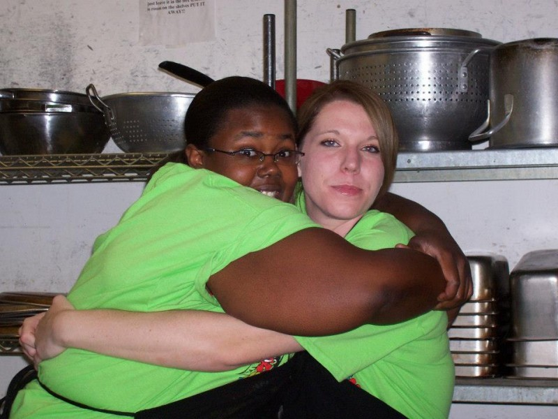 two women hug wearing green shirts hug in kitchen