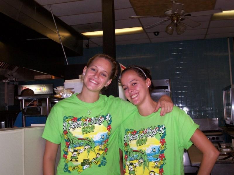 two friends hug at bingo in green shirts