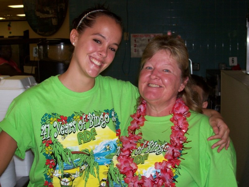 a pair of women hug in lime green shirts