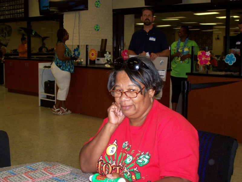 woman with bingo cards eyes camera