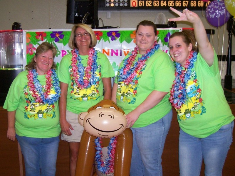 group of women in leis hold inflatable monkey