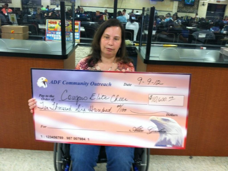 woman in wheelchair holds giant check
