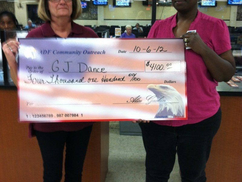 two women display a large american flag check