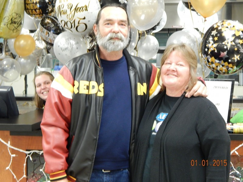 man in a redskins coat poses with woman