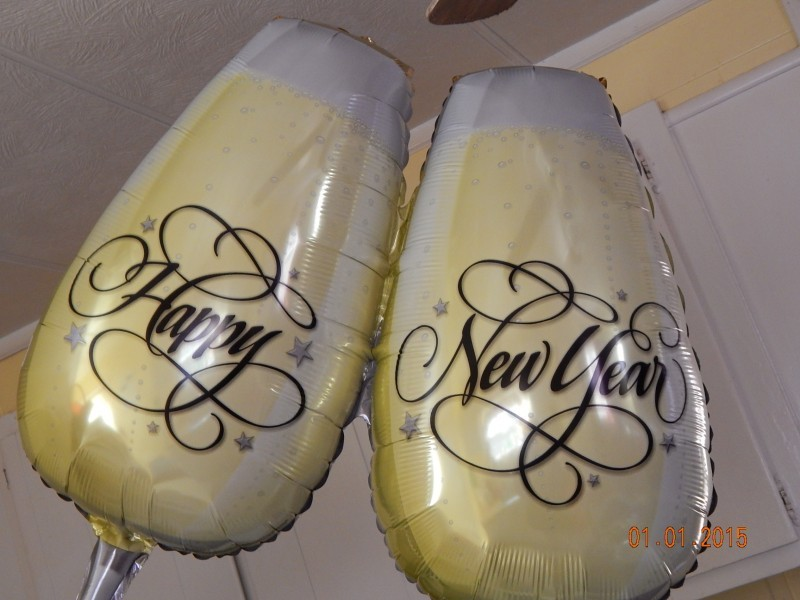 cheers glasses as new years balloons