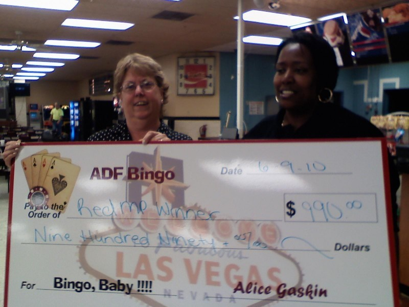 two women hold bingo check