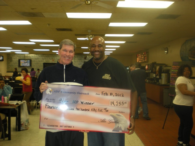 men hold giant check with flack background
