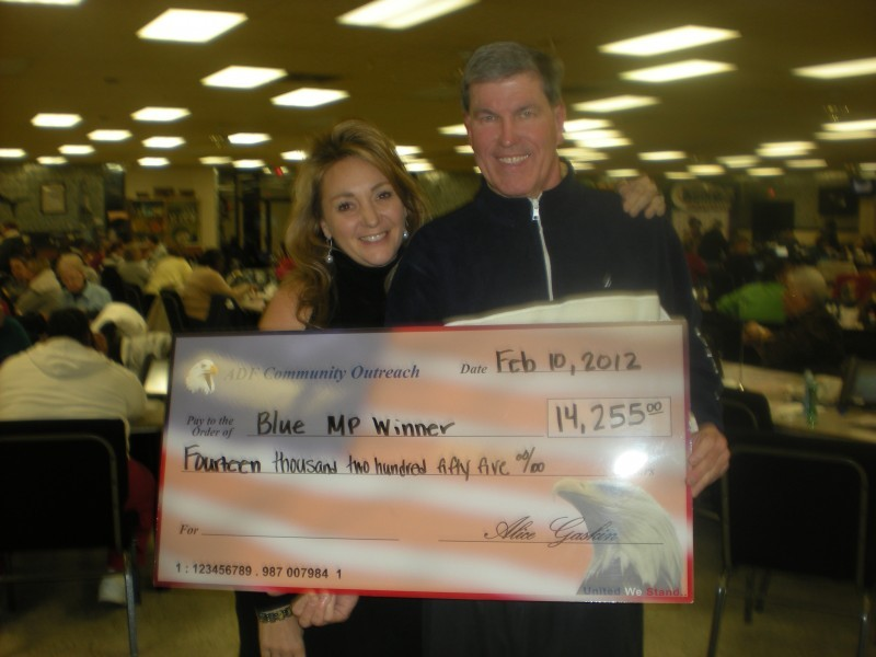 man and wife smile while holding huge check