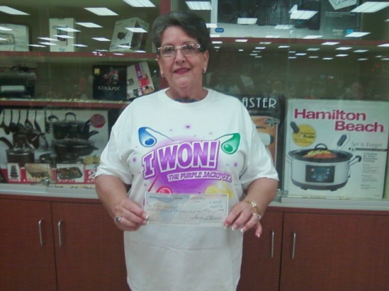 woman in I won shirt holds a check