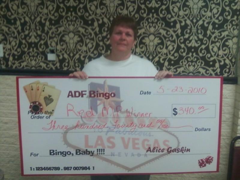 woman proudly shows bingo winnings
