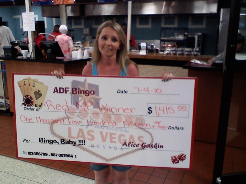 smiling woman shows large bingo check