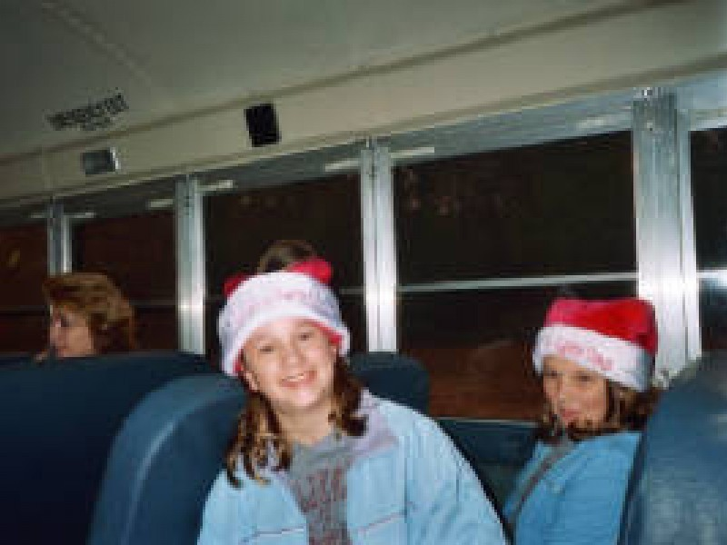 two kids pose in santa hats on a schoolbus