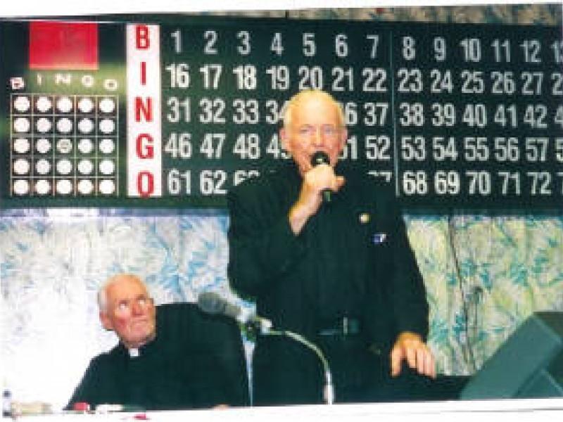a man dressed in black announcing bingo numbers