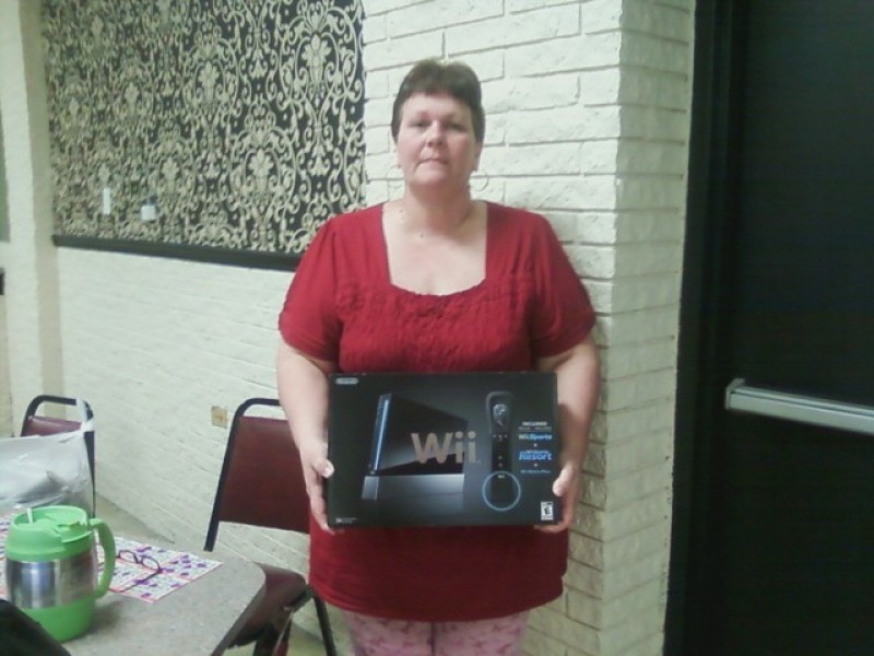 woman poses with a wii prize