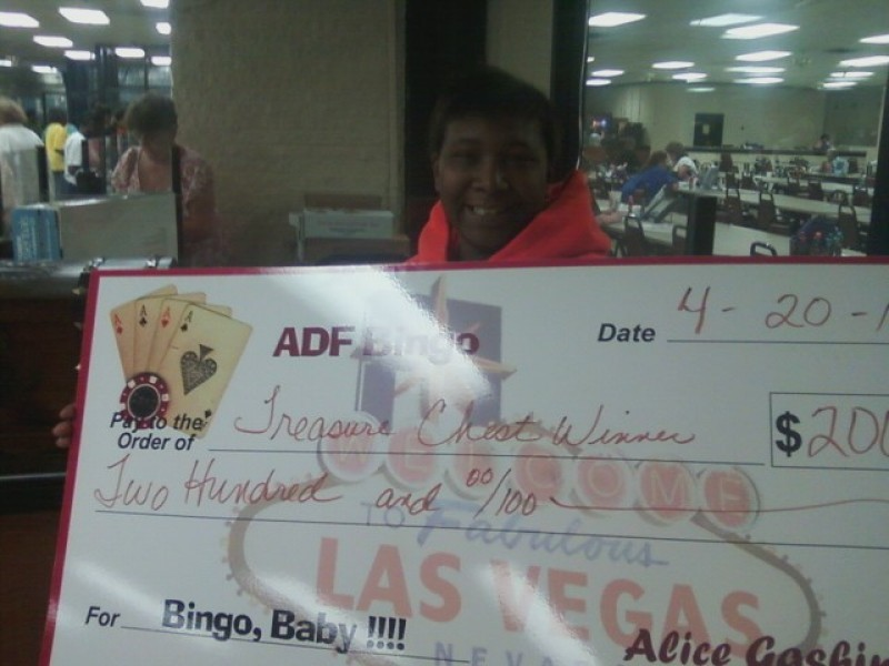 woman smiles while holding check prize winnings