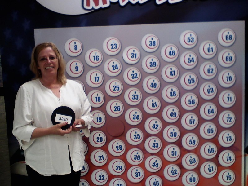 smiling woman holds a money ball winner in front of wall of money balls