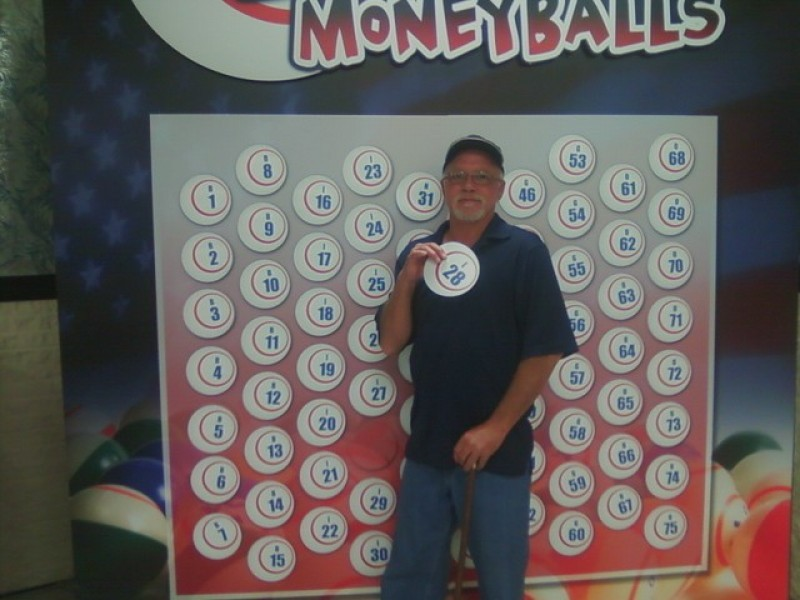 smiling man holds a money ball #28 in front of wall of money balls