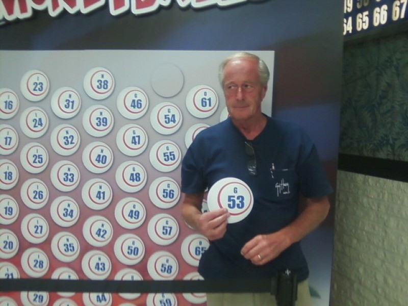 smiling man holds a money ball #53 in front of wall of money balls