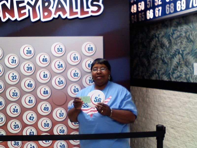 smiling woman holds a money ball #36 in front of wall of money balls