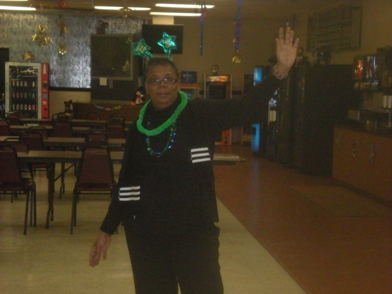 woman in black with green lei and green star headwear