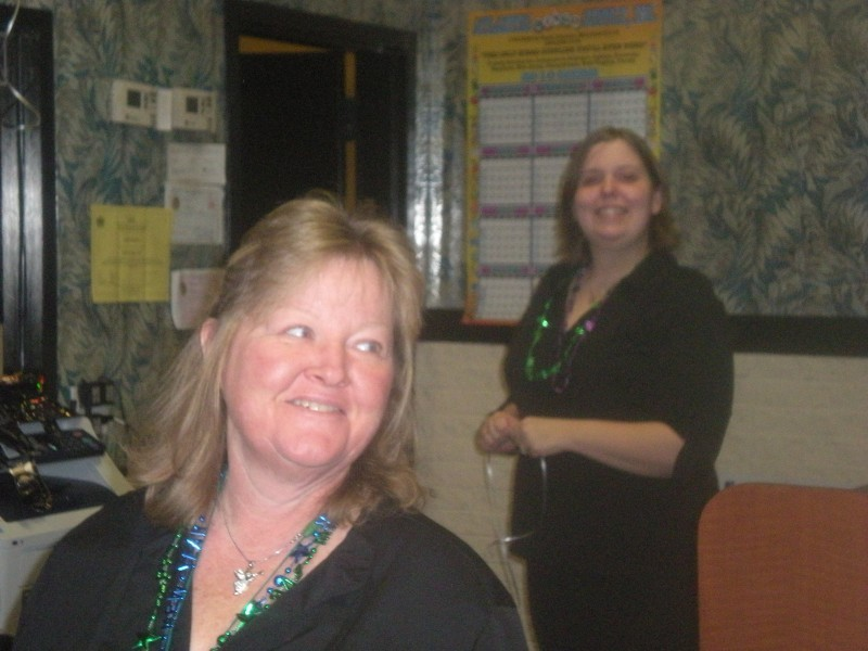a woman in the foreground and a women in the background in green leis