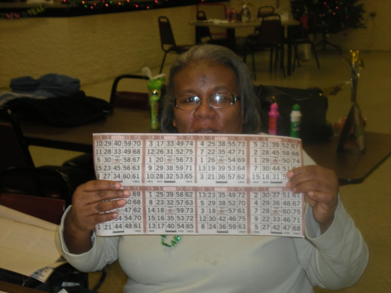 woman holds up a set of bingo cards