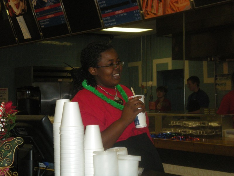 woman in green lei holds a drink
