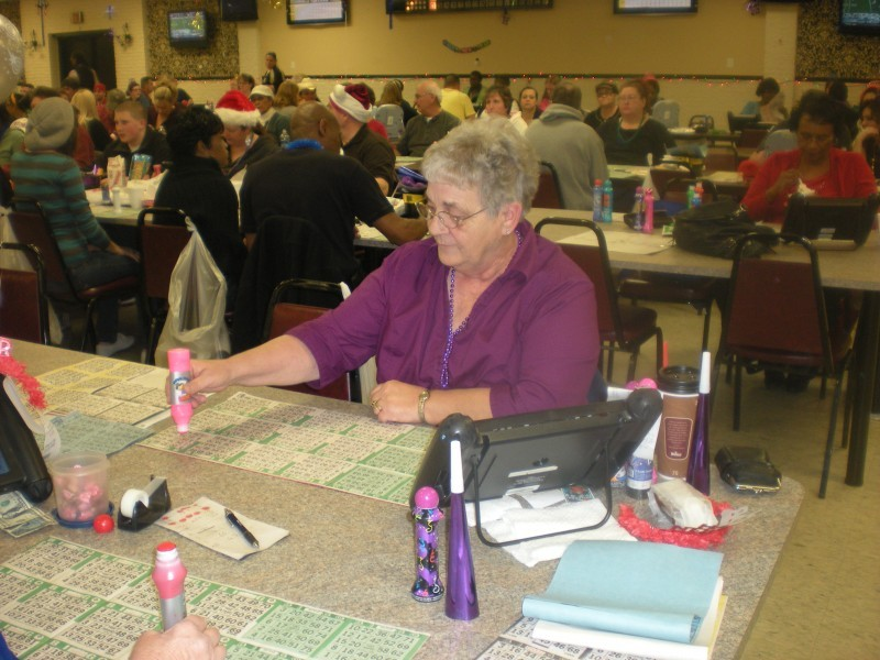 woman stamps bingo cards with pink stamp