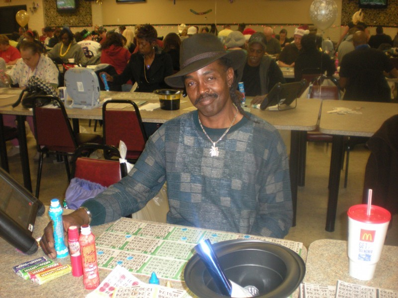 man in brown hat with bingo cards