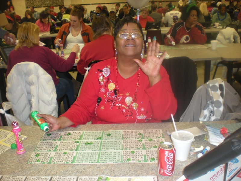 woman at bingo waves at camera