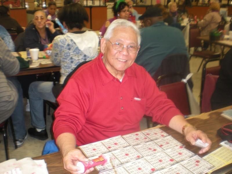man wearing red shirt smiles while playing bingo