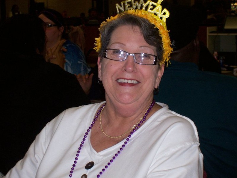 woman with glasses and yellow new years head gear