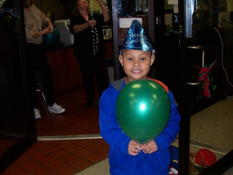 boy in party hat holds a green balloon